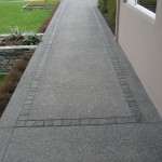 Exposed aggregate concrete with basalt set insert
